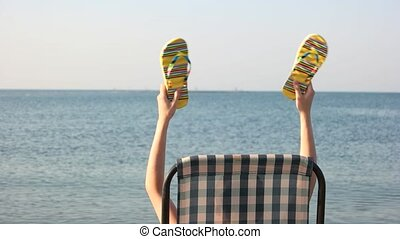 Woman sitting in chaise lounge and waving her flip flops....