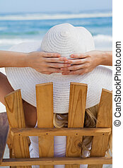 Woman sitting in deck chair at the beach