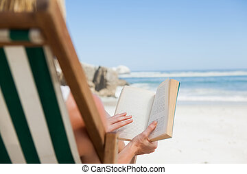 Woman sitting in deck chair at the beach reading