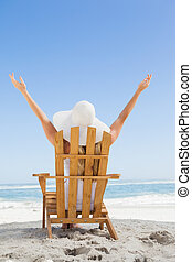 Woman sitting in deck chair at the beach with arms up