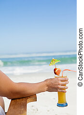 Woman sitting in deck chair with a cocktail at the beach
