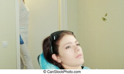 woman sitting in dentist chair, doctor enters, smiles