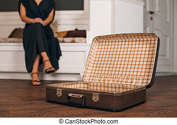 Woman sitting in front of an open suitcase .
