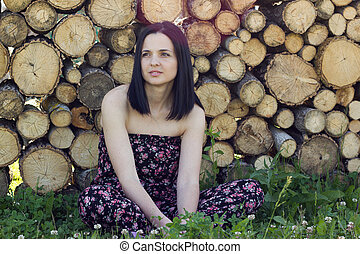 Woman sitting in front of logs