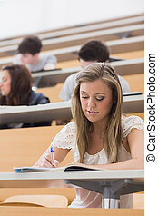 Woman sitting in lecture while writing notes