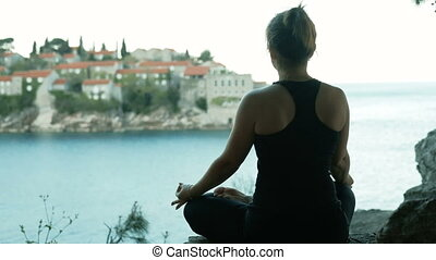 Woman sitting in lotus pose on the background of the city and the sea.
