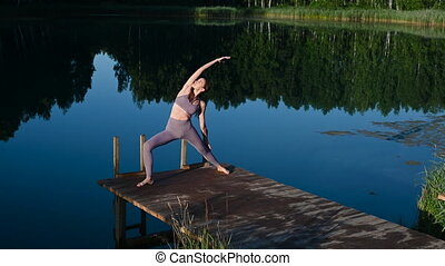 Woman sitting in lotus position and doing yoga on lake background. Beautiful girl exercising outdoors. Stretching exercises and flexibility. Sport and healthy lifestyle concept