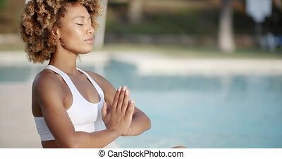 Woman Sitting In Meditating Position - Close up portrait of...