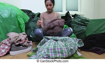 Woman sitting in messy room and sorting old clothes