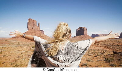 woman sitting in Monument Valley with red rocks overview, raising her arms.
