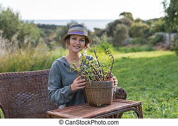 Woman sitting in nature with  plant