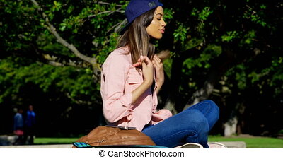 Woman sitting in park on a sunny day 4k