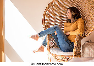 Woman sitting in rattan chair at home - Optimistic woman ...