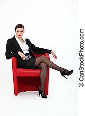 Woman sitting in red chair