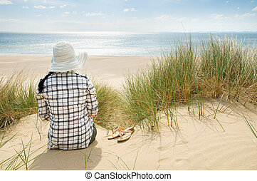 woman sitting in sand dunes looking at sea
