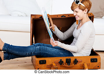 Woman Sitting In Suitcase While Looking At Map