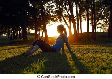 Woman sitting in the glow of the setting sun - Woman sitting...