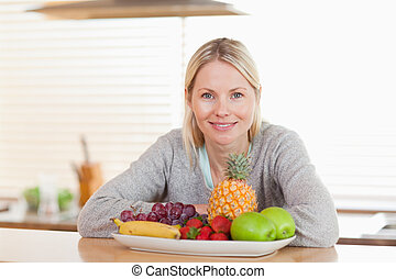 Woman sitting in the kitchen with a plate of fruits