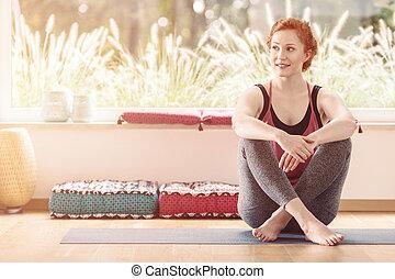 Woman sitting in yoga classroom