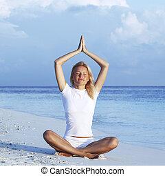 Woman sitting in yoga pose on beach