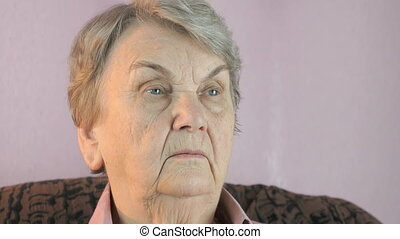 Woman sitting indoors covers face her hands - Elderly woman...
