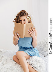 Woman sitting indoors on bed covering face with book.
