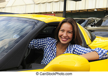 happy woman sitting inside of her new yellow sports car