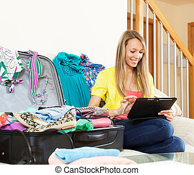 woman sitting  near suitcase while using digital tablet