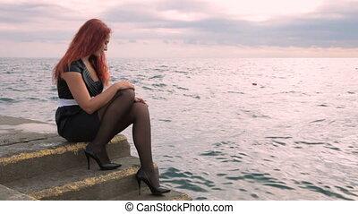 Woman sitting near the sea