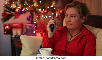 Portrait of a lonely woman sitting on sofa near the christmas tree and watching tv