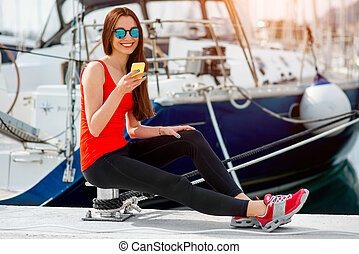 Woman sitting near the yachts - Young sport woman using...