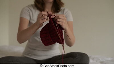 Woman sitting on a bed and knitting
