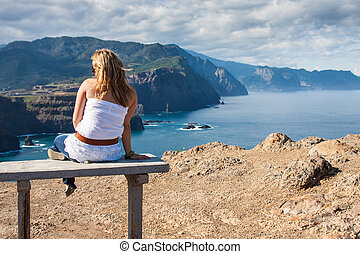 woman sitting on a bench overlooking Oregon coast and Cannon Beach - late afternoon light