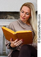 woman sitting on a bench reading.
