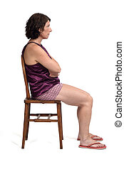 woman sitting on a chair dressed in a short summer pajamas on white background, arms crossed