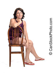woman sitting on a chair dressed in a short summer pajamas on white background