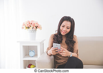Woman sitting on a couch, holding a cellphone.