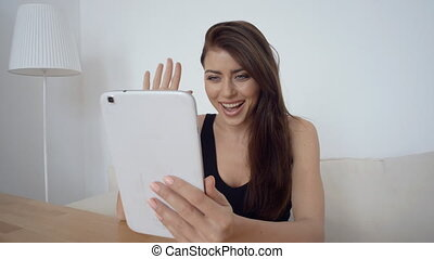 Woman, sitting on a couch, talking to someone using tablet, video conferencing online