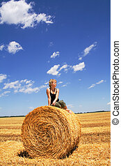 Woman sitting on a hay bale