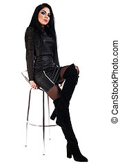 Woman sitting on a high chair in black leather dress