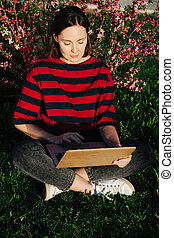 Woman sitting on a lawn working on her laptop, leaning on blossoming bush