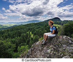 Woman sitting on a mountain peak