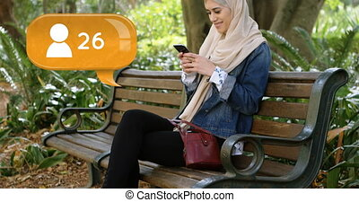 Woman sitting on a park bench texting on her phone 4k