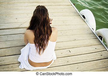 Young unrecognizable woman sitting in a pier near the water surface.