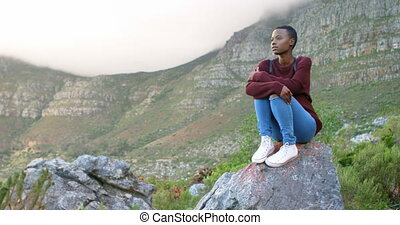 Woman sitting on a rock at countryside 4k - Young woman...