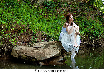 Woman sitting on a rock by the river