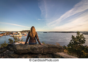 Woman sitting on a rock looking at the fjord and the city in Kristiansand.