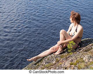 woman sitting on a rock