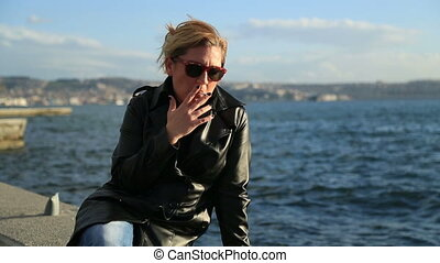 Woman sitting on a seaside and smok