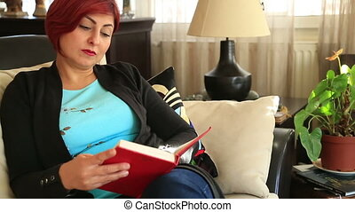 Woman sitting on a sofa and reading a book